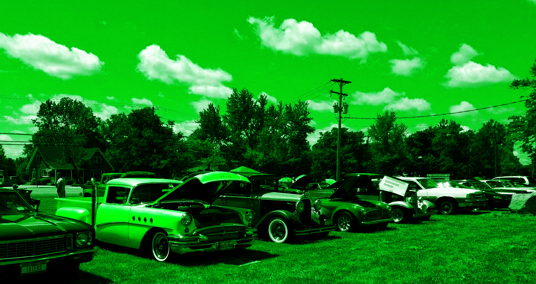 Cars parked on green grass at a car show with clear sky and clouds